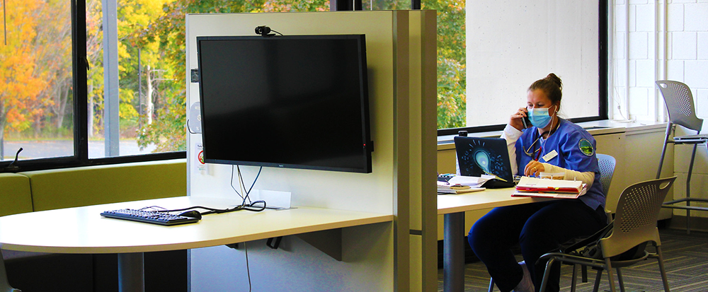 A student sits at a desk using a laptop to study. On the facing side, a widescreen monitor is connected to a keyboard and mouse