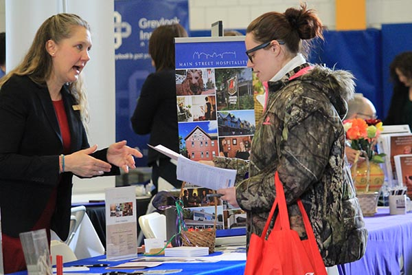 Woman visiting exhibitor table at BCC 2019 Spring Career Fair